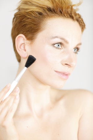 Attractive young woman applying make up on an isolated background Stock Photo