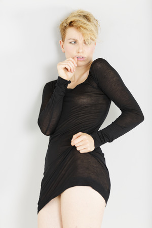 Beautiful young woman in a sheer black dress looking concerned or worried