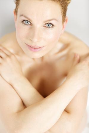mujer desnuda sentada: Joven y bella mujer que cubre su pecho en un estilo belleza pose sentada en un piso de madera en casa