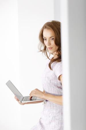 replying: Attractive young woman in a purple dress holding and using a modern laptop computer