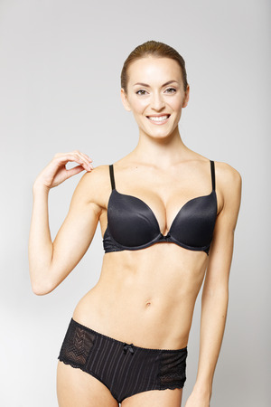 girl bra: Attractive young woman in black underwear on an isolated background smiling