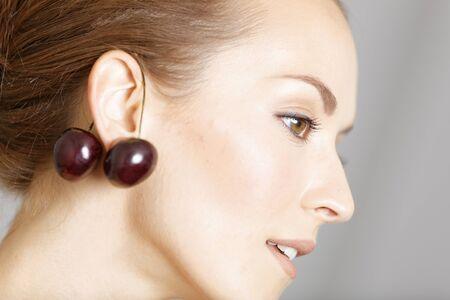 ear rings: Attractive young woman wearing cherries as ear rings