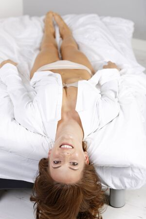 woman looking: Attractive young woman lying on her bed at home in underwear relaxing and having fun Stock Photo