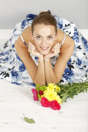 the admirer: beautiful young woman sitting on the floor in a summer dress with a bouquet of fresh flowers