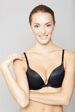 figura humana: Mujer joven atractiva en ropa interior negro sobre un fondo aislado sonriendo Foto de archivo