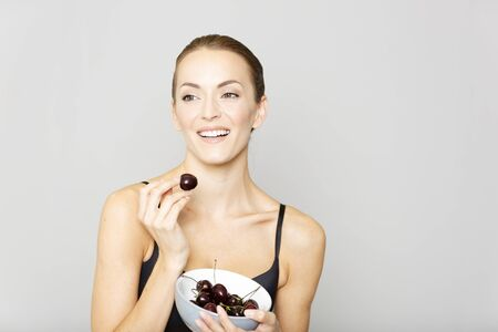 femme en sous vetements: Beautiful young woman in black underwear eating fresh cherries from a bowl Banque d'images