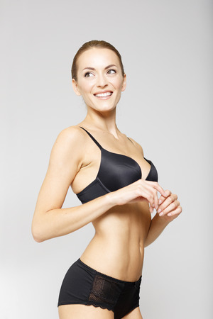 Attractive young woman in black underwear on an isolated background smiling