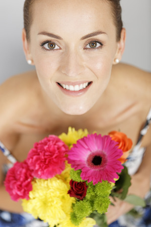 the admirer: Beautiful young woman in a summer dress holding a fresh bouquet of flowers smiling