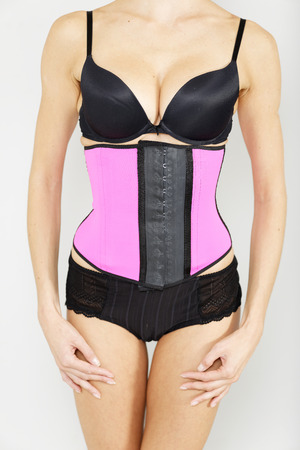 craze: Young woman wearing a waist training corset in black underwear which is the new craze for looking slim Stock Photo