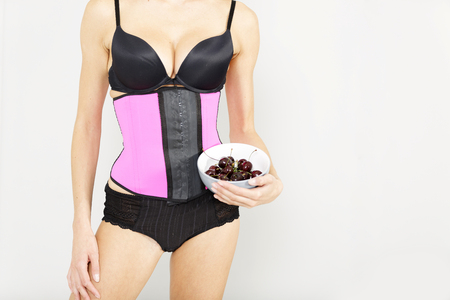 Young woman wearing a waist training corset in black underwear which is the new craze for looking slim Stock Photo