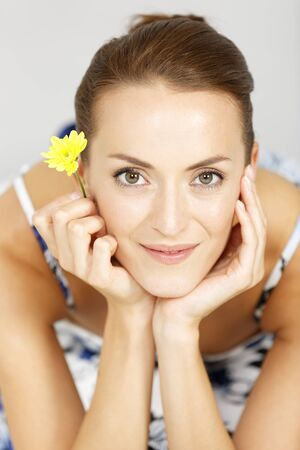 the admirer: Beautiful young woman holding a single fresh yellow flower smiling Stock Photo