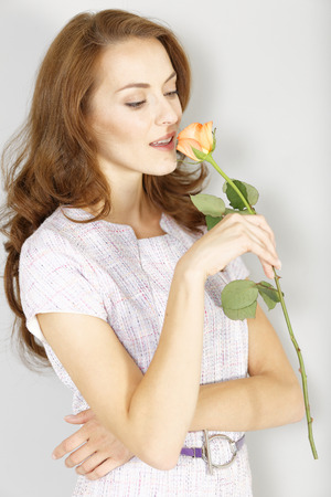the admirer: Beautiful young woman holding a fresh rose and in love Stock Photo