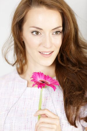 the admirer: Romantic looking woman holding a fresh red flower smiling