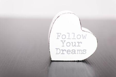 eslogan: Un solo corazón de madera blanca con el lema sigue sus sueños en el frente