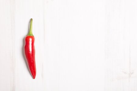 wooden surface: Fresh red chilli on a light wooden kitchen work surface