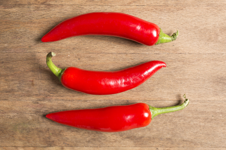 chili: Selection of fresh red chilli on a wooden kitchen work surface