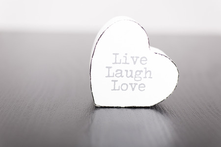 Single white wooden heart with the slogan live laugh love on the front Stock Photo