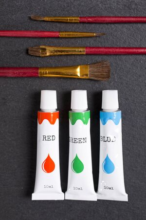 selection: Selection of red green blue paint oils with brushes on a black slate surface