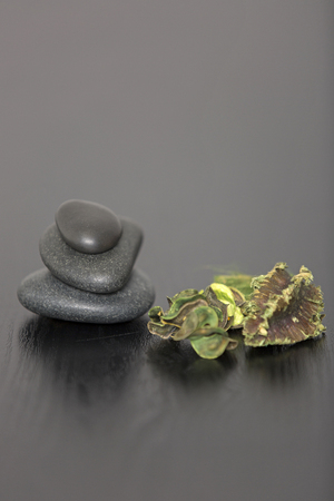 Pile of three spa stones with dried scented leaves