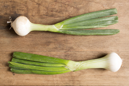 bulb and stem vegetables: Tasty raw spring onions on a wooden kitchen work top Stock Photo