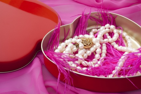 pearls in a heart-shaped box on a pink background photo