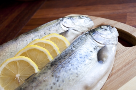 Fresh fishes with lemon on wooden cutting board Stock Photo - 18544164