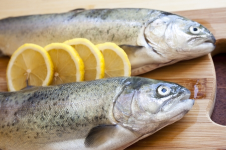 Fresh fishes with lemon on wooden cutting board Stock Photo - 18544166