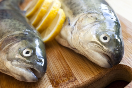 Fresh fishes with lemon on wooden cutting board Stock Photo - 18544168