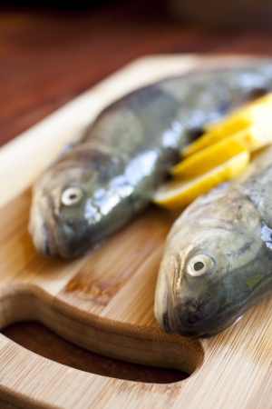 Fresh fishes with lemon on wooden cutting board Stock Photo - 18544163