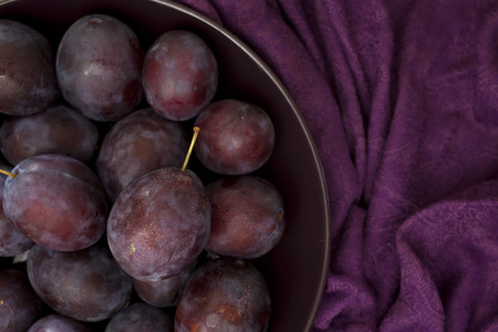Ripe plums on a plate - dark purple composition Stock Photo