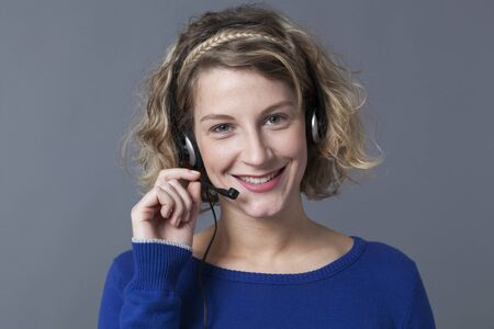 answer phone: satisfied 20s woman wearing a headset to answer phone calls Stock Photo