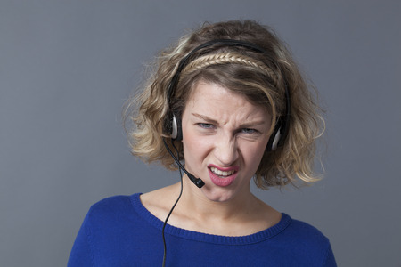 conflicted: displeased young female professional working for a call center