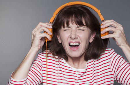 loud music: mature woman suffering from listening to loud music on headphone Stock Photo