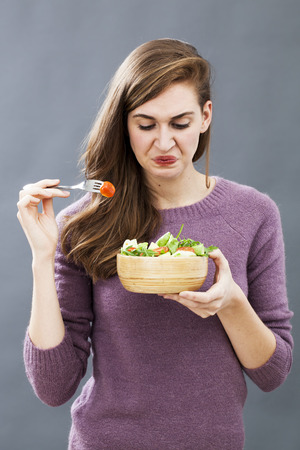 displeased young girl being picky at eating mixed green salad with cherry tomatoes as vegetarian diet