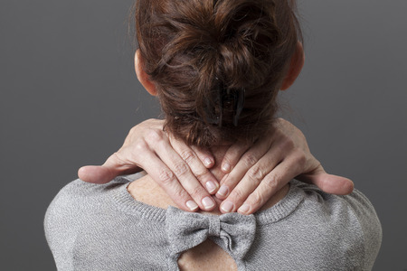 the backbone: back view on mature woman having tensions in a backbone Stock Photo