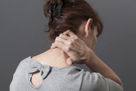 the backbone: mature woman massaging her backbone for relief Stock Photo