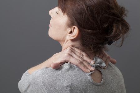 50 代女性の頭部と背骨のリラクゼーションのための彼女の頭に傾いて