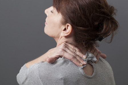 50s vrouw leunend haar hoofd voor hoofd en ruggengraat ontspanning Stockfoto