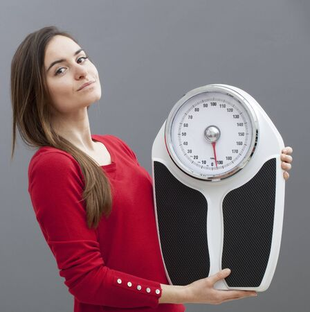 kilos: chic 20s girl standing next to her weighting scale for kilos or pounds control Stock Photo