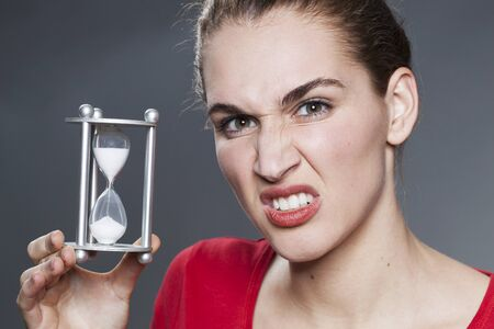 scowl: aggressive beautiful young woman holding egg timer for concept of time management