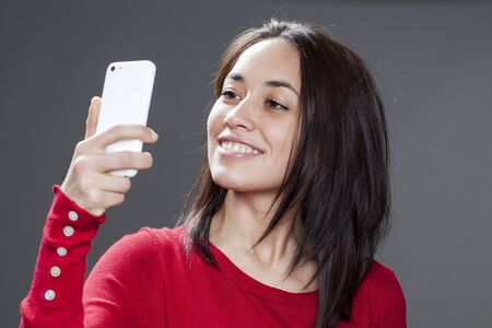 seriousness: beautiful young woman posing with seriousness for self-portrait with phone Stock Photo