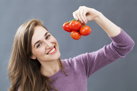 tomate: heureux magnifique jeune femme tenant raisin de tomates pour la sant� de l�gumes et une bonne nutrition