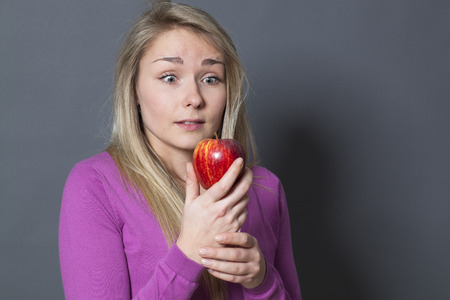 resisting: pretty young blonde woman with a red apple on her hands acting surprised