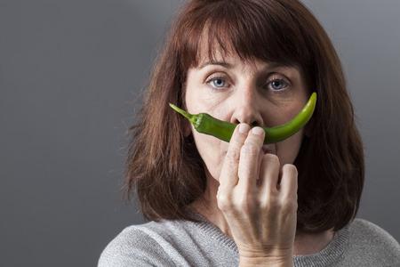salud sexual: cr�tico hermosa mujer madura que sostiene la pimienta verde como el bigote para el concepto de salud sexual