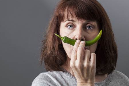sexual health: critical beautiful mature woman holding green pepper as moustache for sexual health concept