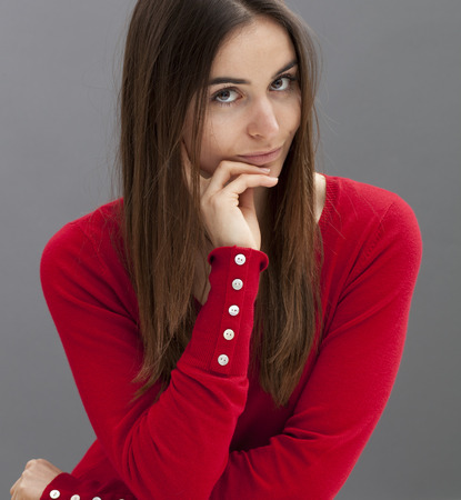 skeptical: skeptical young girl with long brown hair and smart red sweater looking straight with hands holding her face for reflection