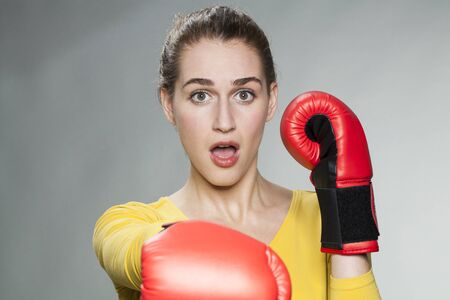 conflicting: surprised young woman punching with boxing gloves for self-defense concept Stock Photo