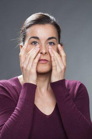 30s: beautiful 30s woman touching her eyes for anti-dark ring skincare or eye allergies Stock Photo
