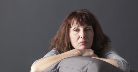 personas pensando: mujer madura abrumado que se reclina la cara y las manos que se establecen en los cojines para su comodidad al estar enfermo o deprimido