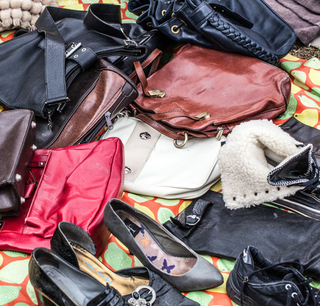 second hand: mix of second hand leather women purses and bags on sale at garage sale on grass for welfare, recycling or selling for cheap to cope with over-consumption and fashion
